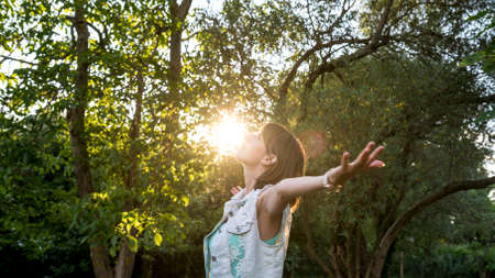 outspread: Woman meditating in nature standing with outspread arms as the rising sun touches her face in a woodland setting , upper body in profile. Stock Photo