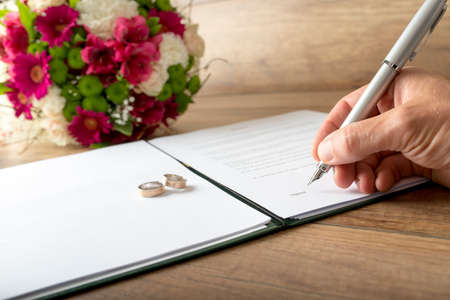 marriage certificate: Man signing a marriage register as a groom or witness with a stylish fountain pen with two wedding rings and red flowers, symbolic of love. Stock Photo