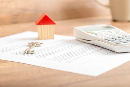 Llave de la casa de plata acostado en un contrato para la venta de la casa, contrato de arrendamiento, seguros o hipoteca en un concepto de bienes raíces, vista de ángulo bajo, con especial atención a la punta. Foto de archivo