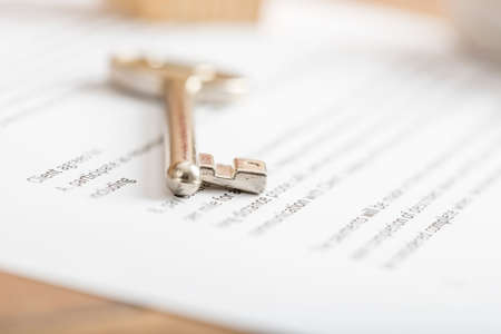 key: Metal house key on a contract of house sale in a real estate conceptual image. Stock Photo