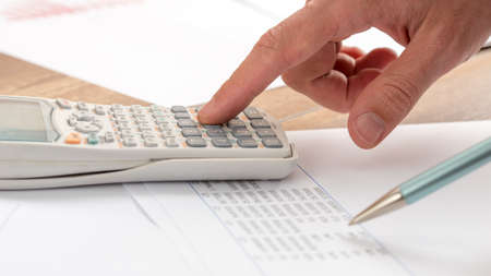 Closeup of accountant doing a calculation on a white calculator.