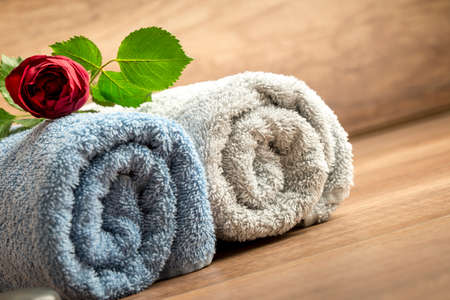 sensual massage: Romantic Spa Still Life Concept with a Beautiful Fresh Red Rose on Top of Two Rolled Towels with a Wooden Background.