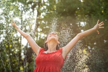 우드랜드 환경에서 민소매 빨간 드레스에 뻗은 팔로 물 제트기 아래에 서있는 여자를 기쁘게합니다.