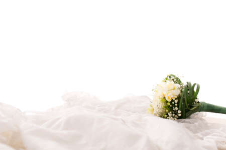 corsage: Side Profile View of Bridal Bouquet or Corsage of White Flowers on Soft White Fabric Wedding Gown with Copy Space and White Background.