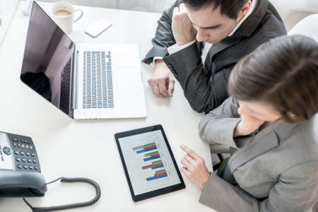 statistical: Top view of male and female business partners analysing statistical annual report represented in graphs on digital tablet. Stock Photo