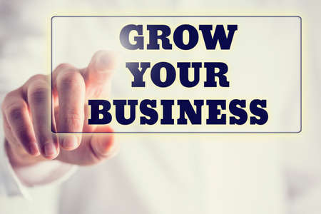 grow: Concept of new or start up business - words Grow your business on a virtual interface in a navigation bar with a determined businessman touching it with his finger from behind.