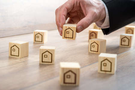 Businessman Hand Arranging Small Wooden Cubes with House Drawings on Top of the Table for Realty Concept. Stock Photo