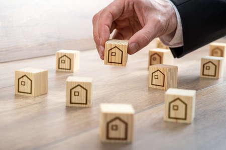 Geschäftsmann Hand Arrangieren Kleine hölzerne Würfel mit Haus Zeichnungen auf oben in der Tabelle für die Immo Konzept.