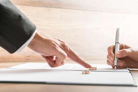 Männliche Hand drücken Sie einen Ehering über einem weiblichen Hand über die Scheidungspapiere zu unterzeichnen. Konzeptionelle Scheidung oder Ehe.
