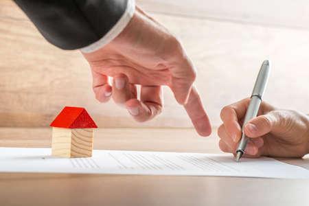 彼のクライアントの家の売却や住宅ローンの紙の契約書にサインする場所を示す不動産業者のクローズ アップ。不動産の概念に適しています。