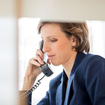 縦断ビューの固定電話では電話をかける彼女の机に座って成功した若い実業家の内部事務所パーティションを表示します。