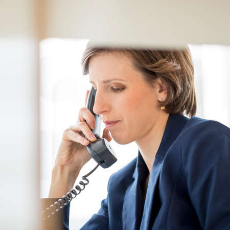 answering phone: View through an internal office partition of a successful young businesswoman sitting at her desk making a phone call on a landline telephone, profile view. Stock Photo