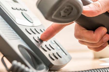 Primer plano de vendedor de telemarketing masculino que sostiene un número de teléfono de marcación auricular del teléfono para hacer una llamada de negocios.