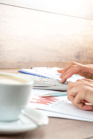 statistical: Closeup of female hands making mathematical and statistical calculations on white desk calculator while proofreading financial graphs with a cup of hot coffee alongside.