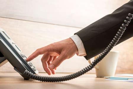 Close-up van mannelijke telemarketing operator vormen van een telefoonnummer op een klassieke zwarte vaste telefoon, geschikt voor klantenondersteuning en klantenservice concepten. Stockfoto