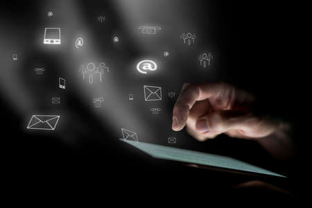 Male hand hovers over digital tablet, illuminated by screen. White communications icons float on black background in misty light. Stock Photo
