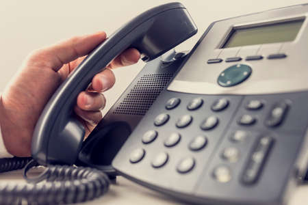 recepcionista: Primer plano de operador masculina a punto de responder a una llamada de teléfono mientras se toma un auricular de un teléfono fijo negro clásico. Efecto de filtro retro.