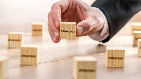 estrategia: Conceptual del hombre de negocios Mano que sostiene Cubo de madera con la Estrategia de texto en la parte superior de la tabla con otros bloques.