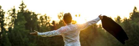 그의 팔을 서 흰색 셔츠에서 사업가 한 손 축하 생명 또는 저녁 태양 광선에 의해 백라이트 성공에 정장 재킷을 들고 펼쳐진.