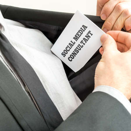 consultants: Social media consultant removing a white business card from the inner pocket of his elegant jacket.