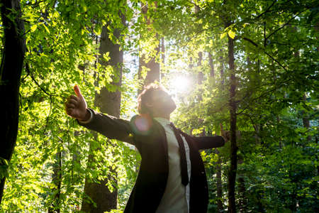 low angle view: Businessman standing with his arms outspread showing thumbs up sign celebrating business success in woodland with fresh green leaves on the trees backlit by the rays of the sun, low angle view.