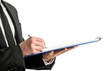흰 셔츠, 검은 양복과 넥타이 클립 보드에 흰색 배경에 은색 펜으로 쓰는 비즈니스 남자의 중간 섹션 측면보기.