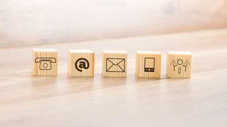 テーブルの上に配置された連絡先イラストの盛り合わせと小さな木のブロックを閉じます。 写真素材