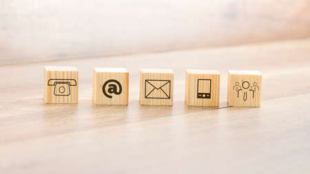 Close up Small Wooden Blocks with Assorted Contact Illustrations Arranged on Top of the Table.