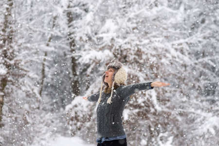 arms wide open: Happy young woman embracing beautiful life with her arms wide open as she is standing outside in a snowy winter woodland with snowflakes falling.