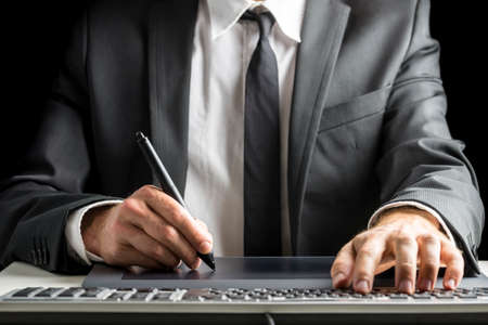 view of an elegant office: Front view of male graphic designer or photographer  in an elegant suit sitting at his office desk working with stylus pen on digital tablet and simultaneously using computer keyboard.