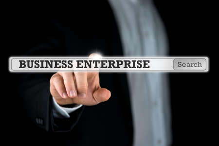 navigation bar: Business enterprise written in a navigation bar on a virtual interface or computer screen with a businessman reaching out his finger to activate the search button from behind. Stock Photo