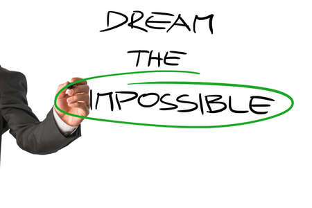 motivator: Personal motivator writing a Dream the impossible message, with a special emphasis on the word Impossible,  on a white virtual screen encouraging you to allow yourself to live to your full potential. Stock Photo