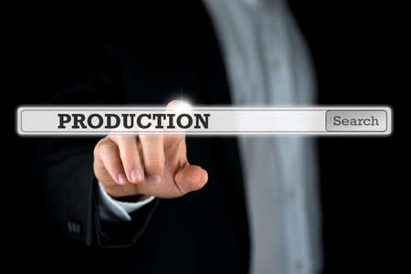 activating: Businessman activating a search bar with the word Production on a virtual computer screen or interface. Stock Photo