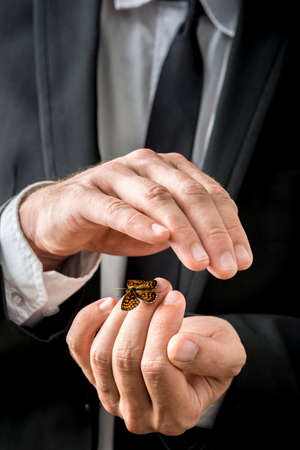 settled: Businessman nurturing a butterfly that has settled on his fingers carefully cupping his hand over the top in a conceptual image.