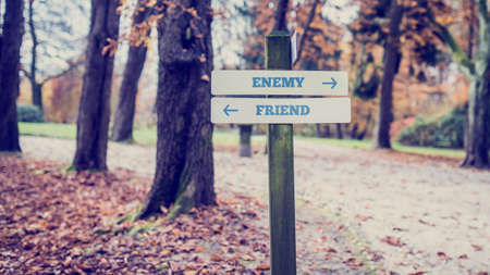 enemy: Signpost in a park or forested area with arrows pointing two opposite directions towards Enemy and Friend. With retro filter effect.
