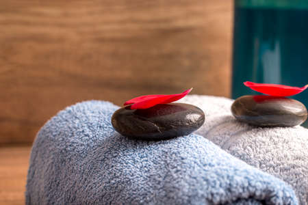Luxurious spa arrangement for two with a a blue and white folded soft towel, black massage stones with red rose petal on top and a bottle of massage oil or moisturizing lotion.