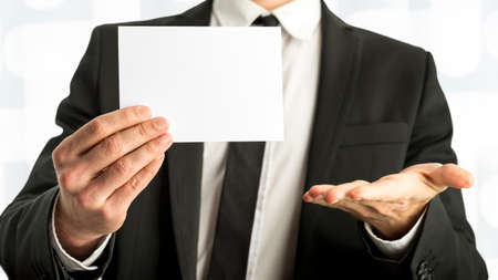 trades: Close up Businessman Holding a Plain Card with Copy Space with One Hand Open Against White Background.