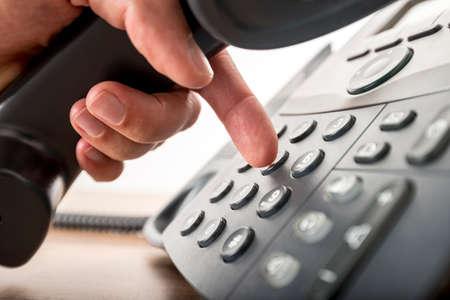 llamando: Primer plano de la marcación de un número de teléfono en un teléfono fijo negro. Conceptual de la comunicación global, el apoyo empresarial y atención al cliente.