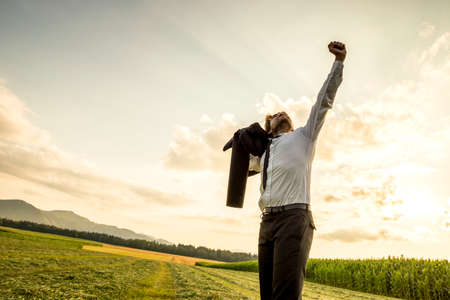relieved: Thankful Young Businessman Standing in the Green Field and Raising his Arm While Looking Up the Sky for Success. Stock Photo