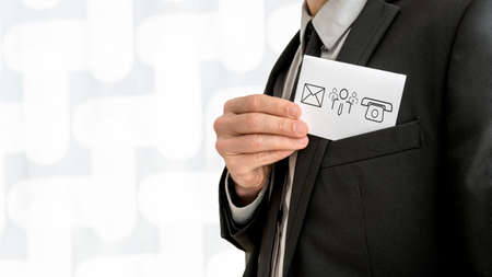 removing: Personal business consultant  removing a business card with communication and people icons - phone, email and contact center icon - from the inner pocket of his jacket, close up view.