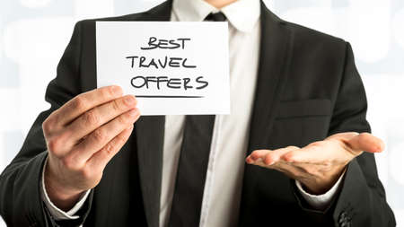 best travel destinations: Close up Businessman Holding Small Paper with Best Travel Offers Message Against White Background. Stock Photo