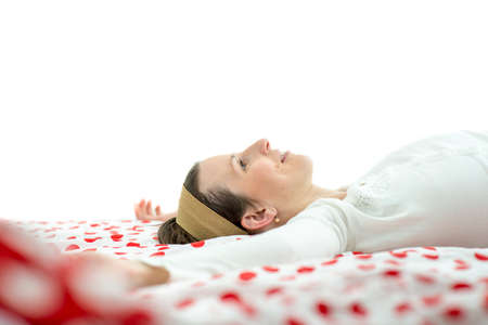bedspread: Low angle view of a young woman wearing a headband lying resting on a bed with a colorful red and white polka dot bedspread relaxing after a stressful day, with plenty of copyspace. Stock Photo