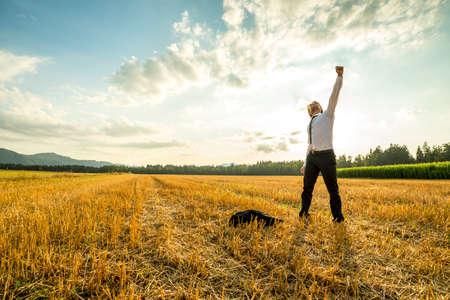 Jonge zakenman staande in het veld en het verhogen van zijn arm voor succes tijdens het werpen van zijn jas op de grond. Stockfoto