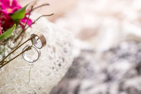 Close Up of Two Wedding Rings Hanging on Twigs of Bridal Bouquet with Fuchsia Colored Flowers in a Traditional Symbol of Love and Commitment in Wedding Ceremony. Stock Photo