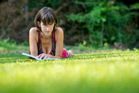 frontal view: Young woman relaxing on her stomach reading on the fresh green spring grass in a leafy garden, frontal low angle view. Stock Photo