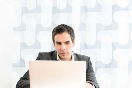 front angle: Front view of a young businessman in a high key office typing information or reading a document on a white laptop computer,  low angle view from the back of the computer.