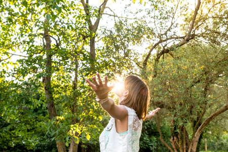 떠오르는 태양의 프로필에 숲 설정, 상체에 그녀의 얼굴을 만지는으로 명상 그녀의 팔에 서 그녀의 아름다운 삶을 껴안은 젊은 여자가 펼쳐진.
