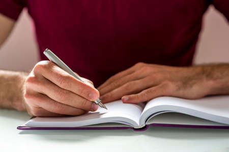 article writing: Close up Hand of a Man Writing Something on a Clean Notebook on Top of the Table.