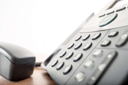 Primo piano angolata vista di un telefono fisso nero con un tastierino numerico e il portatile o il ricevitore sganciato nel servizio al cliente e le relazioni concept. Archivio Fotografico - 43575950