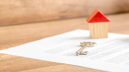 Silver house key lying on a contract of house sale, lease, insurance or mortgage in a real estate concept, viewed low angle with focus to the tip.
